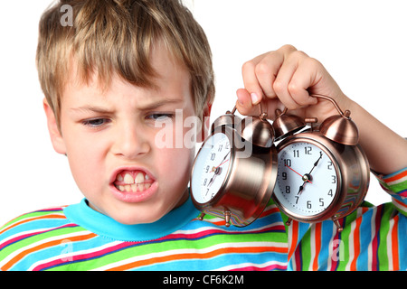 Little emotional blond boy in striped shirt holds two alarms near head - Stock Photo