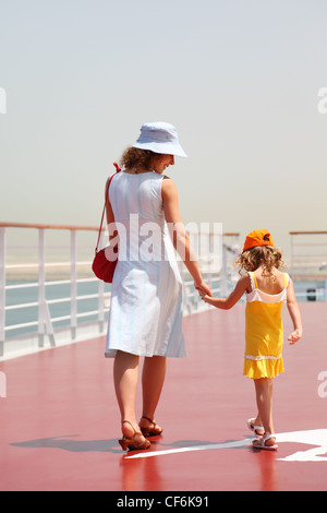 young mother and daughter walking on cruise liner deck, sunny day, view from back - Stock Photo