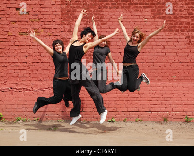 Four girls in same black clothes jumping on background of brick wall - Stock Photo