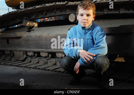 Little boy in blue jacket sitting near crawler tractor in the dark - Stock Photo