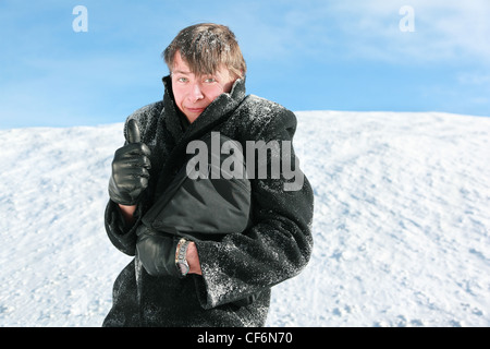 Fellow stands in winter on snow holds  brief-case and shows gesture fingers - Stock Photo