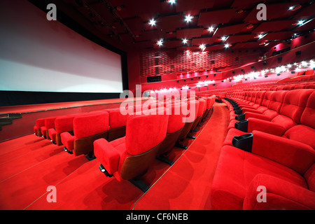 View from stairs on rows of comfortable red chairs in illuminate red room cinema - Stock Photo