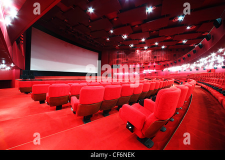 View from stairs on screen and rows of comfortable red chairs in illuminate red room cinema - Stock Photo