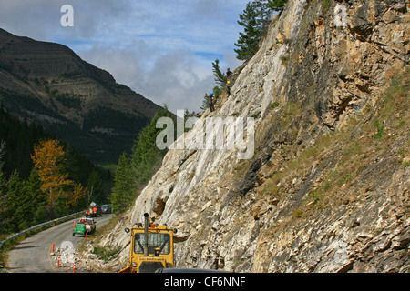 Cleaning up a rock slide from a mountain roadway - Stock Photo