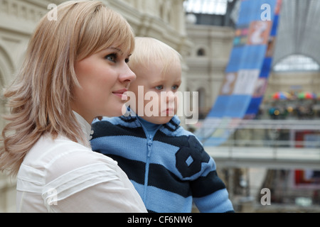 Portrait of the young woman with child on hands. Look aside. Indoors. - Stock Photo