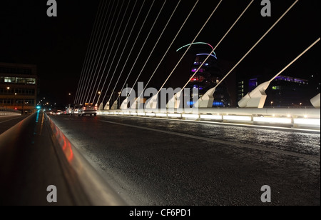 ╨бars go over Samuel Beckett Bridge Samuel Beckett Bridge is cable-stayed bridge in Dublin that joins Sir John Rogerson's - Stock Photo