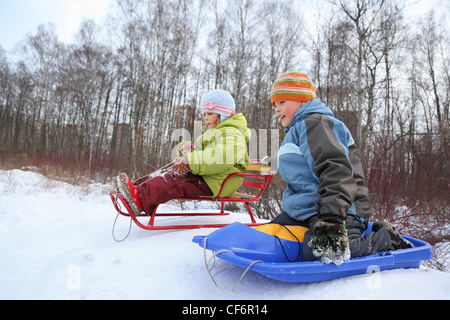 Brother and sister intend  drive from  hill in winter on sledges, focus on  brother - Stock Photo