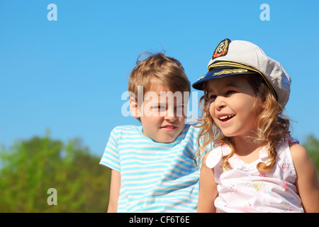 little girl with captain cap and boy at sunny day - Stock Photo