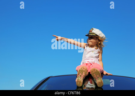 little girl sitting on car roof showing by finger on left side, blue sky - Stock Photo