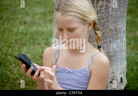 MFemale child with blonde hair in two plaits sitting against tree trunk looking down at mobile phone dialing numbers - Stock Photo