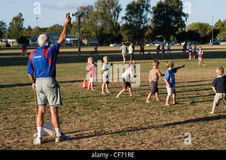 chidren running the 100 meters on sports day with family watching - Stock Photo