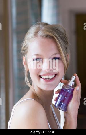 Female wearing purple eyeshadow holding bottle of purple perfume - Stock Photo