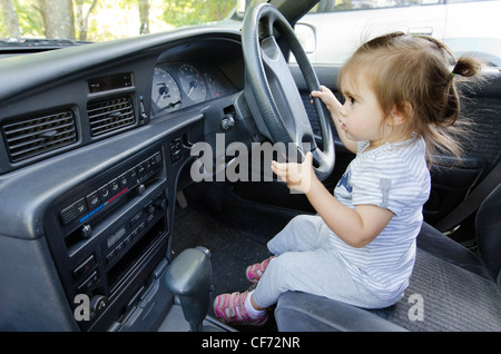 A little girl driving car. - Stock Photo