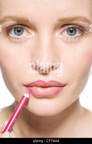 Female applying pink pencil lipliner to her lips, unsmiling, looking at camera - Stock Photo