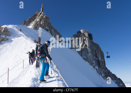 Man climbing down arete from aiguilles du midi cable car station carrying skis on rucksack on the way to the valley - Stock Photo