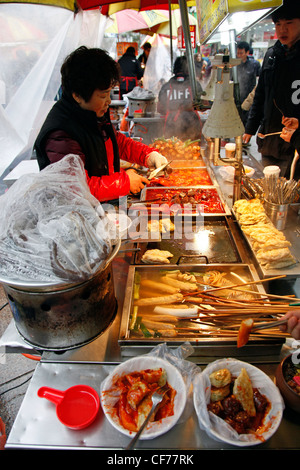Street vendors selling traditional Korean food from stalls in Busan, South Korea - Stock Photo