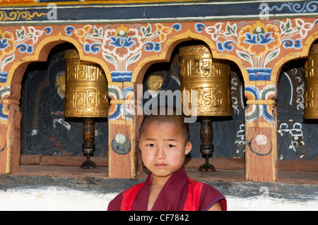 Infantile Buddhist monk standing by the prayer mills in the Temple of Fertility Chimi Lhakhang, Lobesa, Bhutan - Stock Photo