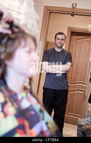 Tired Caucasian Russian bridegroom waiting for bride during wedding preparations in domestic room - Stock Photo