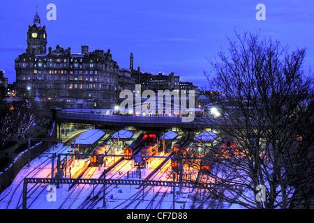 Waverley station at dusk in winter snow, Princes St, Edinburgh, Scotland, UK @HotpixUK - Stock Photo
