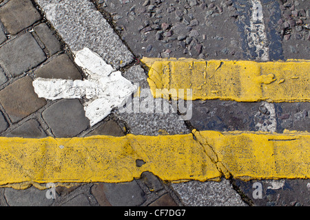 Detail of road markings painted on a pedestrian crossing: a white arrow pointing right and yellow lines. - Stock Photo