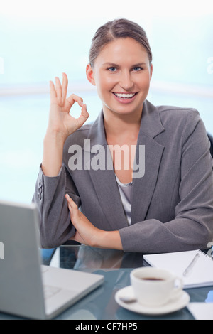 Portrait of a businesswoman signing that everything is okay - Stock Photo