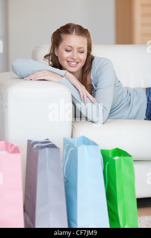 Young woman taking a moment off on her couch after a shopping tour - Stock Photo