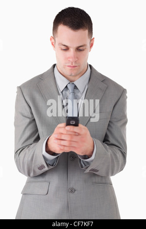 Portrait of a businessman dialing on his cellphone - Stock Photo