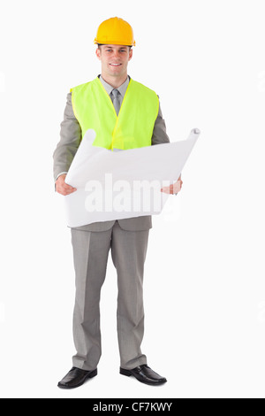 Portrait of a smiling architect looking a plan - Stock Photo