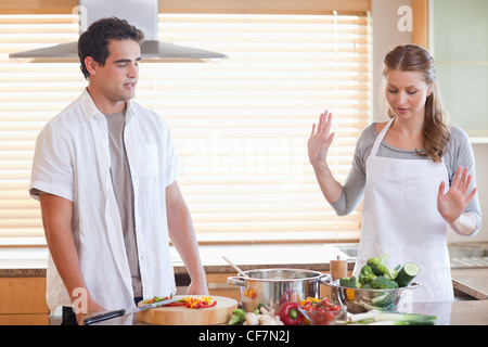 Couple having a disagreement in the kitchen - Stock Photo