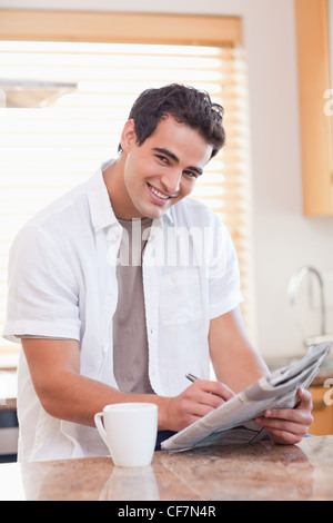 Smiling man doing crossword puzzle in the kitchen - Stock Photo