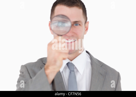 Young businessman looking through a magnifying glass - Stock Photo