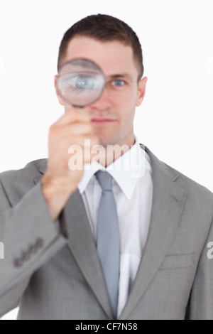 Portrait of a businessman looking through a magnifying glass - Stock Photo