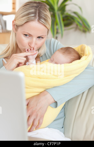 Mother kissing her baby's hand while looking at the laptop - Stock Photo