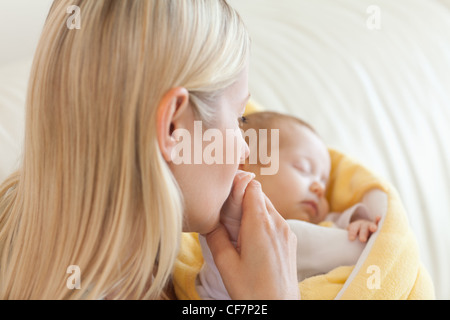 Above view of mother kissing her baby's hand - Stock Photo