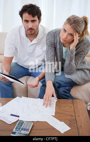 Portrait of a worried young couple looking at their bills - Stock Photo