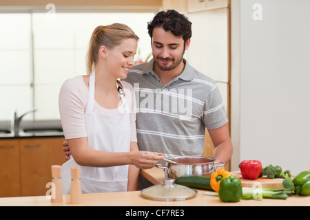 Lovely couple preparing a sauce - Stock Photo