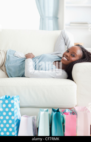 Woman lying on sofa after shopping - Stock Photo