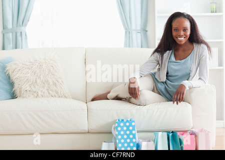 Woman on sofa with shopping in front of her