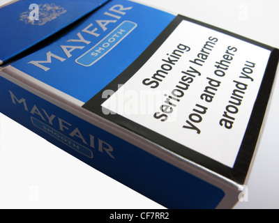 A cigarette packet with a warning on about seriously harming yourself by smoking - Stock Photo