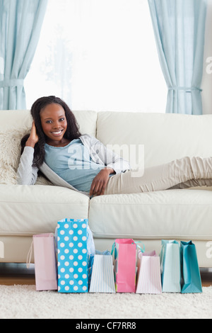 Woman relaxing on sofa after shopping - Stock Photo