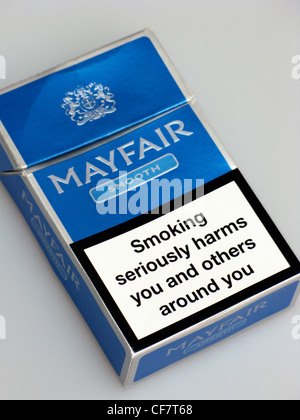 A cigarette packet with a warning on indicating a doctor or pharmacist can help you to quit smoking - Stock Photo