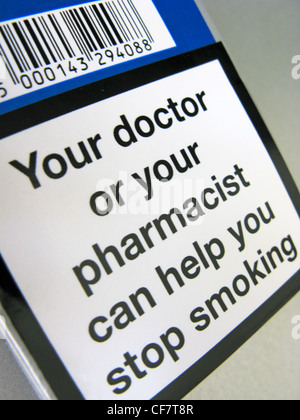 A cigarette packet with a warning on, indicating a doctor or pharmacist can help you to quit smoking - Stock Photo