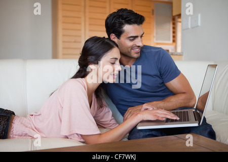 Charming young couple using a laptop - Stock Photo