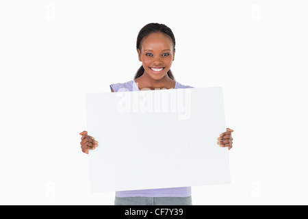 Woman holding placeholder in her hands on white background - Stock Photo