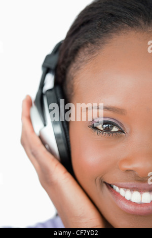 Close up of young woman with headphones on white background - Stock Photo
