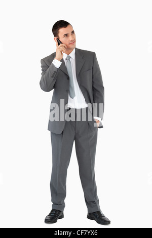 Businessman listening to caller against a white background - Stock Photo