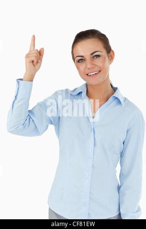Smiling businesswoman pointing upwards - Stock Photo