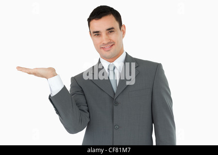 Businessman displaying something in his palm - Stock Photo
