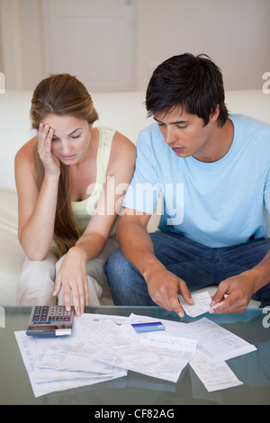 Portrait of a worried couple looking at their bills - Stock Photo