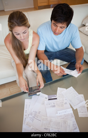 Portrait of a young couple looking at their bills - Stock Photo